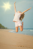 Flying jumping beach girl at blue sea shore Stock Photos