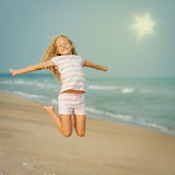 Flying jumping beach girl at blue sea shore. In summer vacation in the day time Stock Images