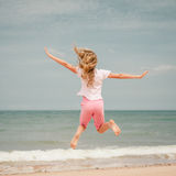 Flying jumping beach girl at blue sea shore Royalty Free Stock Image