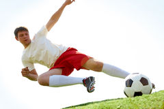 Flying kick. Portrait of soccer player making flying kick at ball during game stock image