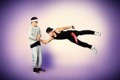 Flying kick. Two modern dancers dancing hip-hop at studio Royalty Free Stock Photos