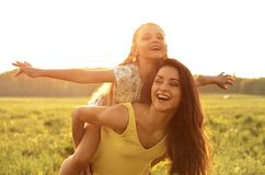 Flying kid girl laughing on the happy enjoying mother back on su Stock Images