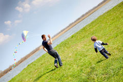 Flying a kite. Happy dad and son flying a kite together Royalty Free Stock Image