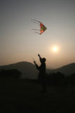 Flying Kite. Man flying kite with the setting sun Royalty Free Stock Photography