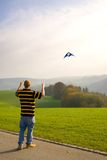 Flying a kite. Man flies a kite in the autums breeze Royalty Free Stock Photo