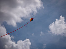 A flying kite. A kite flying under a cloudy sky Stock Photos