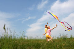 Flying kite. Children flying rainbow kite in the meadow on a blue sky background Royalty Free Stock Photos