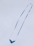 Flying kite. Blue kite soaring in the sky Royalty Free Stock Photo