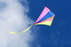 Flying kite. A kite flying against a blue sky in sunlight, bright colors and streaming tail Royalty Free Stock Photos
