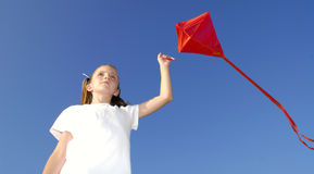 Flying a Kite. Girl flying a kite in a park with blue sky Stock Photo