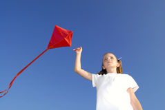 Flying a Kite. Girl flying a kite in a park with blue sky Stock Photography