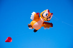 Flying Kite. A big flying kite in shape of an owl with the blue sky in the background Royalty Free Stock Images