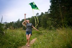 Flying a kite. European girl runs with a kite in the field. Summer day royalty free stock photo
