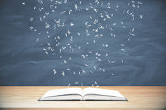 Flying letters from the opened book on wooden table at blackboard Royalty Free Stock Images