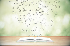 Flying letters from the opened book on wooden table Royalty Free Stock Images