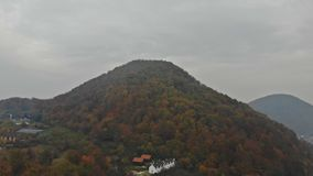 Flying through the light evening mist and aerial view of mountains and valleys covered with autumn forests. Majestic mountains landscape under morning, flying stock video footage
