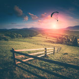 Flying in a light of sunset. Instagram stylisation. Paraglide silhouette flying over Carpathian misty mountains in a light of sunset. Instagram stylisation Stock Photos