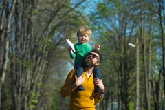 Flying like bird. Little son dream of flying on fathers shoulder. Child boy and father launch paper plane in park. Flying like bird. Little son dream of flying royalty free stock photos