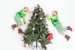 Flying little elves decorating Christmas tree. Santa`s helpers Stock Photography