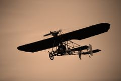 Flying Machine. A very old airplane in flight Stock Photos