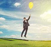 Flying man with yellow balloon Royalty Free Stock Photos