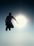 Flying man. Young man falling. Silhouette of poise man. Flying man. Young man falling down over Sun in colorful sky. Silhouette of poise man and beautiful sunset stock photo