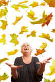 Flying maple leaves. Happy senior woman with many colorful maple leaves Royalty Free Stock Image
