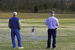 Flying model helicopter. Man flying model helicopter at local park,friend watching Stock Photo