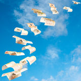Flying money. Uk ten pound notes shot as if flying away into a blue sky Royalty Free Stock Photos