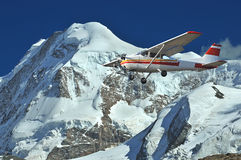 Flying in the mountains. A light aircraft flies past the summit of an ice covered mountain giving a fantastic view Royalty Free Stock Photography