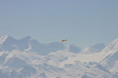 Flying in the mountains. A yellow plane equipped with skis flying in the Swiss mountains Royalty Free Stock Image