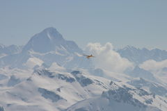 Flying in the mountains. A yellow plane equipped with skis flying in the Swiss mountains Royalty Free Stock Images