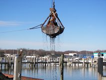 Flying Mud. Crane bucket carrying a dripping load of lake bottom mud Royalty Free Stock Photos