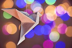 Flying origami bird in a bokeh background stock photo