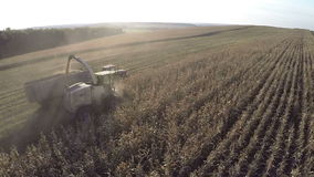 Flying over agricultural works in the field. RYAZAN, RUSSIA - SEPTEMBER 13, 2015: Aerial shot of gathering crops on farmland. Combine and tractor busy on harvest stock video