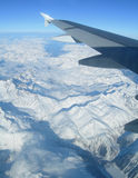 Flying over the Alps. View of airplane wing over snow capped mountains Royalty Free Stock Photography