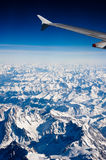 Flying over the Alps. Aerial view of snow capped Alps mountains between Switzerland and Italy Stock Images