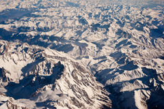 Flying over the Alps. Aerial view of snow capped Alps mountains between Switzerland and Italy Royalty Free Stock Images
