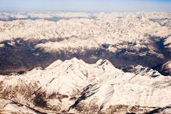 Flying over the Alps. Aerial view of snow capped Alps mountains between Switzerland and Italy Royalty Free Stock Photo