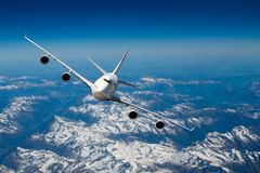 Flying over the Alps. Huge four engines airplane flying over the Alps Stock Photos