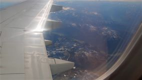 Flying over the Alps. Mountains view through the plane wing flying over Austria stock footage