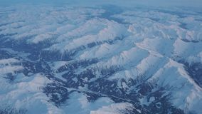 Flying over the Alps during the sunset in winter time. Aerial view from the airplane window stock footage