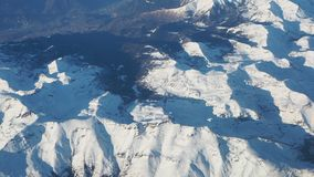 Flying over the Alps during the sunset in winter time. Aerial view from the airplane window stock video footage