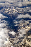 Flying over the Alps to Rome. Air travel over Europe, flying over the Alps toward Italy with snow covered mountains and light cloud Stock Photo