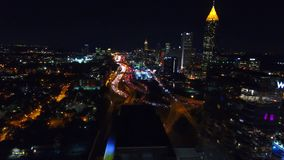 Flying over Atlanta commerial buildings. The view of nighttime downtown and freeway with traffic below. left motion stock video footage