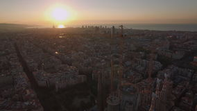 Flying over Barcelona and Sagrada Familia at sunset stock footage