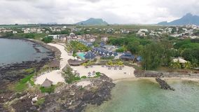 Flying over the beach with local and tourist people in Mauritius, Flic en Flac area. Hotel Architecture and Beach umbrella stock video footage
