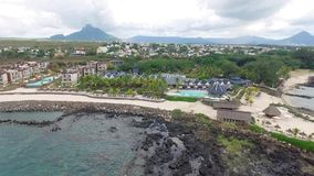 Flying over the beach with local and tourist people in Mauritius, Flic en Flac area. Hotel Architecture and Beach umbrella stock video