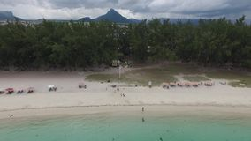 Flying over the beach with local and tourist people in Mauritius, Flic en Flac area. Many yacht and boats in water stock video footage