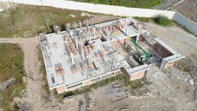 Flying over a brick house under construction. Construction workers build a house of brick. New house aerial view stock video